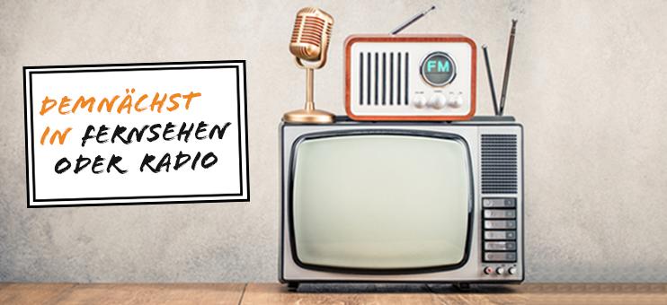 Die Grafik zeigt ein Retro-Fernsehgerät, auf dem ein ebenfalls Retro-Radio und ein Mikrofon stehenh. Links daneben steht auf einem Schild: Demnächst in Fernsehen